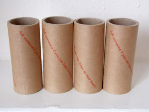 "Photo of four cardboard tubes arranged upright in a row, printed with the words ""Ask someone if you can listen to their heart."""