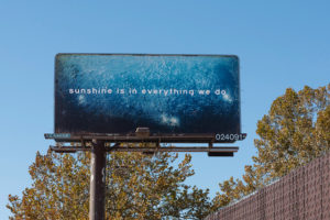 "Photo of a roadside advertising billboard against a blue sky. The billboard contains a photo pf sparkling blue water with the words, ""sunshine is in everything we do."""